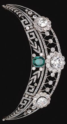 A Belle Epoque emerald and diamond tiara, circa 1910. The upper tier of openwork trellis design millegrain-set throughout with rose diamonds, and decorated with three flower head cluster motifs set with circular-cut diamonds, the lower tier of foliate and meander design, set with similarly-cut stones and centring on an octagonal emerald. By family tradition it is understood that this tiara was worn at an official dinner given by Kaiser Wilhelm II by an ancestor of the formerly owner.