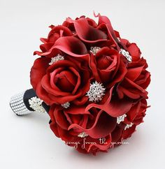 """This custom silk flower bridal bouquet is 9"""" in diameter and includes red real touch roses and deep red real touch mini calla lilies adorned with assorted rhinestone buttons. The edge of the bouquet is finished with loops of grey satin ribbon.  The handle is wrapped in black satin accented with a rhinestone brooch and bands of diamond mesh.  This bouquet is accompanied by a boutonniere for the groom of a red rose bud accented with a rhinestone and finished with a black stem wrap.  If you…"""