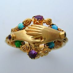 A Regency gemset Gimmel (betrothal or wedding) ring. The triple yellow gold band connecting to form clasped hands over a heart, within a garnet and turquoise set cannetille work border, gross weight 4.8 grams, circa 1820. ARV