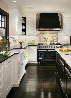 contrasting but complimentary color scheme: white base cabinets/black countertops and black island cabinets with white counters