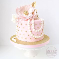 Light pink cake with a string of pearls and a lovely pink flower and gold leaf by Sweet Philosophy Bakery
