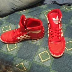 Simple red Adria low profile sneakers by Adidas. Featuring