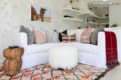 A comfortable sectional makes the most of this corner. The owner travels all over the world. They wanted the guesthouse to reflect an elegant boho blend. The light floor, walls and furniture allowed her to punctuate the space with richly colored accessories. Throw pillows made from vintage Hmong textiles, a blanket from India and a Moroccan rug add layers of global texture.