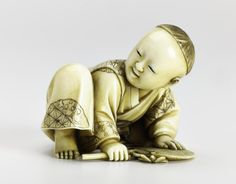Netsuke of carved ivory, a boy crouching with both hands on a fan: Japan, by Seiga, late 19th century