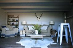 Beautiful rustic summer house and surrounding deck designed by Amelia Wilson Interiors Ltd.