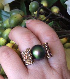 Akribisch handgemachte Ring mit einem großen wunderschönen Swarovski grün facettierte Perle. Die Glasperlen sind genähte einerseits zu einer Zeit, die einzigartige Band - flexibel und leicht aber stark machen. Die Golde tanzen und glitzern. Einzigartigen Schnitt Design gibt die Illusion des atemberaubenden grünen Swarovski Perle free Float. Lassen Sie sich nicht dadurch täuschen, da dies Präzision Sicke mit superstarken Fireline und sehr sicher ist.  Passt wie angegossen und es werden…