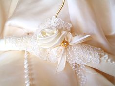 WEDDING DRESS HANGER As something very special and lovely for your wedding dress and its portrait for your photographs, this gorgeous hanger is handmade in a unique and all-orginal design. The hanger is ivory satin, and overlaid with gorgeous ivory vintage lace and a satin ivory rose. There are 2 types of ivory ribbon and a rhinestone embellishment. These hangers are so unique you would be hard pressed to find one like it anywhere, but youll love that you found this one for your…