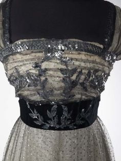 """Evening dress This skirt is part of a dress that is included in Janet Arnold's 'Patterns of Fashion: Englishwomen's dresses and their construction c. 1860-1940' (pages 58-59). Arnold describes it as 'an evening dress in black silk net covered with tiny 1/8"""" silver sequins over an ivory satin underskirt.'  Maker: Madame Hayward Production Date: c. 1909-1910"""