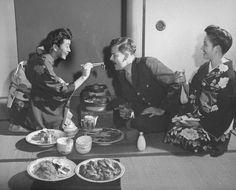 Geisha Yae Murata (L), known as Miss Peach Blossom, feeding a customer