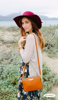 Turn heads this fall in a wide-brim felt hat, blue floral dress, and loose-knit cardigan. Add warm accents like a cross body bag and leather wristwatch to complete the look.