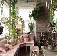 Coral upholstery and green plants meet in a romantic bohemian living room