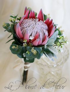 A simply stunning statement bouquet, perfect in all its glorious simplicity. A perfect rusty red King protea surrounded by lush foliage, spinning gum and lambs ear with sprigs of green and white Geraldton wax and gumnuts. This custom silk flower bouquet is approx. 20cm (8) in diameter.