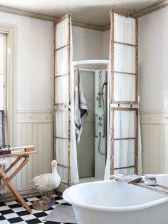 DUSJKABINETT AV GAMLE VINDUER: Paret valgte bort klinkerfliser, men ønsket seg likevel en dusj. Da ble en walk-in dusj det perfekte valget. For å få den til å gli inn blant resten av interiøret, brukte Eija stoff og gamle vindusrammer rundt. På den måten ble ikke dusjen så iøynefallende   LEV LANDLIG
