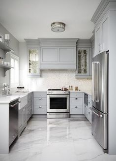 This gray u-shaped kitchen features a gray paneled hood flanked by antiqued mirrored kitchen cabinets and mounted against white and gray mosaic backsplash tiles over a stainless steel oven range.