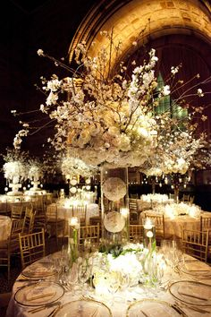 Tall, branching elements, bouquet in vase, cut flowers in vase, flowers arranged on table including submerged flowers with floating candles
