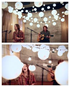 "Simple and bright decor idea: drape several strands of lights in various sizes (small bulbs, medium paper lanterns, etc.) but consistent shapes across a room or stage. Pretty idea for a wedding, bridal shower or even a conference backdrop. Looks good on video and in photos. Other ideas: a sunny baby shower, a senior photo shoot, a family photo or at night for an al fresco backyard party. From Lauren Daigle's YouTube video, ""In Christ Alone (Acoustic)."""