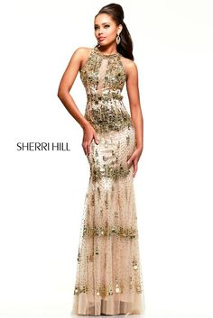 New for 2015...The Sherri Hill 9714 is as much a work of art as is a garment. The long version of style 9703, this look features mosaic tiles and crystals swept over it like a brushstroke of metallic paint. The bodice is heavily plated in mirror gems with a sexy strip of sheer net running down the center. Tapered and fitted with a tiled band at the natural waist, giving way to a tulle fit-and-flare skirt. This amazing, couture quality dress is offered in gold as shown.