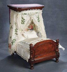 """Theriault's Antique Doll Auctions - French Mahogany Doll's Canopy Bed with Lavish Fittings - 20"""" Of richly-grained mahogany,the bed features superb details of craftsmanship including detailed paneling on all sides of the bed frame, canopy with rounded corners and purple silk accents,and an unusual tapestry backboard of woven silks depicting an 18th-century court scene. Fitted with lavishly with embroidered silks and lace.French, maitrise quality, circa 1860."""