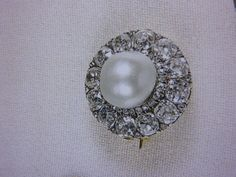 The Queen`s pearl & diamond cluster brooch as seen in Angela Kelly`s book.