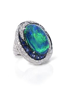 Black Opal, Sapphire and Diamond Ring: Oval-shaped Black Opal mounted with white pave diamonds and round-brilliant-cut sapphires hand-crafted in platinum