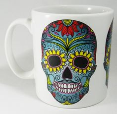 Colourful Day of the Dead Skull Mug. Mug is designed and printed in Britain. 3 traditional coloured skulls around the mug A high quality ceramic mug which is both dishwasher and microwave proof. Height is 9cm, diameter 7.5cm, with a capacity of 270 ml (9oz). From the Series 1 Original Line by Half a Donkey Ltd. www.halfadonkey.co.uk