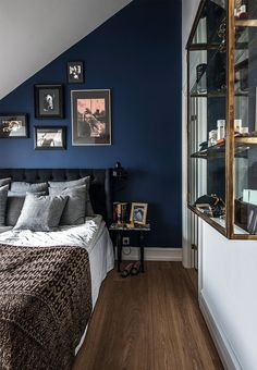 Dark and warm blue colour on the bedroom-wall and an elegant decoration with brass china cabinet and a classic styled headboard.