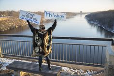 Tereza Holguin, of St. Paul, held up signs as she stood on the outskirts of about 500 people gathered on the Marshall Avenue Bridge (Lake Street) to protest the Dakota Access Pipeline on the border of St. Paul and Minneapolis.