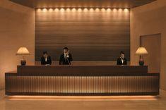 Reception desk design for hotel dark wood desk stone accent wall hi density hi hats modern Hotel Reception Desk, Reception Desk Design, Lobby Reception, Reception Counter, Hotel Lobby Design, Accor Hotel, Spa Luxe, Hotel Restaurant, Hotel Decor
