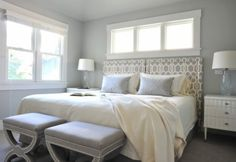 Calling to mind posh Hollywood sets, this bedroom strikes a luxurious note with its serene palette of cream, white and dove gray. A headboard upholstered in a trellis print and pair of X benches with nailhead trim complete the look.