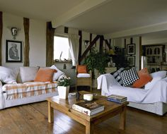 Orange-White Country Living Room A country style sitting room with beams, hardwood floors, sofas, coffee table