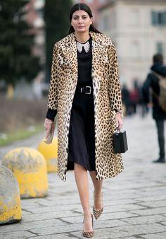 Street style de Giovanna Battaglia com vestido de manda comprida preto com sobretudo de animal print.