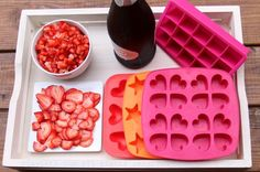 Ice cube trays, sliced and diced berries, and sparkling wine to make fun ice cubes