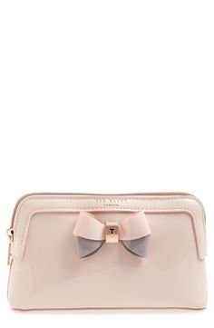 A two-tone bow embellished with polished signature hardware adds a ladylike touch to this glossy cosmetics case cut in a modern, structural silhouette.