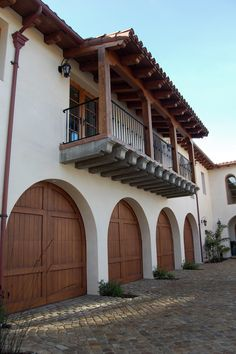 Front Exterior: Spanish architecture, Spanish colonial architecture, Spanish style, Mexican architecture, Mission architecture, Spanish Baroque, old world style, tile roof, detailed fascia, wood overhang, wood eave, wood corbels, smooth stucco, French doors, arch French doors, wood window, balcony, wrought iron railing, wrought iron, decorative iron, exterior wall sconce light, arched wood garage door, Rotunda, paver staircase with wrought iron handrail, stone driveway