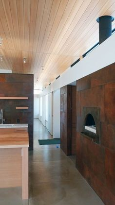 """A pizza oven and built-in storage spaces line a hallway, saving space. houses for single families don't make sense ecologically—or in my opinion, functionally,"""" says Hirsh."""