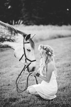 Horse photography session: blonde girl wearing a flower crown and white dress, crouching in front of her grey gelding.