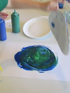 Drip blue and green paint on a paper plate... kids use their hand to turn it on a white sheet of paper... makes an Earth!