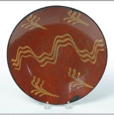 """Garth's Sale 1114 Lot 718. May 17 2014. REDWARE PIE PLATE.  American, mid 19th century. Coggled rim and yellow slip decoration. Edge chips. 10.5""""d.  Estimate $ 200-400."""