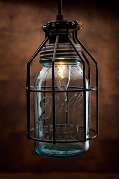This light pendant lamp combines modern style with the vintage flair of 1900's Ball mason jar, surrounded by a rustic cage. This industrial look is perfect for