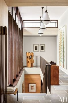 In a stylish Hamptons home devised by Deborah Berke and decorated by Thomas O'Brien, the latter's pendant lights from Aero join an Alexandre Noll sculpture (far end) and a Donald Baechler painting (right) in the entrance hall | archdigest.com