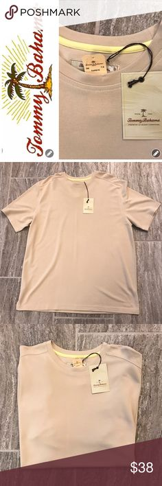 "NWT Men's Tommy Bahama Dress Tee NWT Men's Tommy Bahama Dress Tee is featured in light corozo.. a beige color. It has a scoop neck and tonal stitching. This shirt looks great from casual to dressy. It is in excellent condition. No stains, marks or mars. 85% Tencel Lydcell 15% Polyester. Machine Washable. Length from shoulder to hem 36"". Smoke Free Home. Great Shirt! Tommy Bahama Shirts Tees - Short Sleeve"