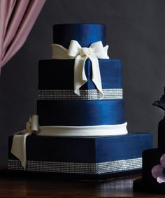 Blue and White Wedding Ideas - SAPPHIRE AND ICE Vanilla bean cake in sapphire fondant, with handmade sugar bows and jewelled banding. 460$. I Do! Wedding Cakes, 2700 Dufferin St., 416-787-6666, idoweddingcakes.ca.