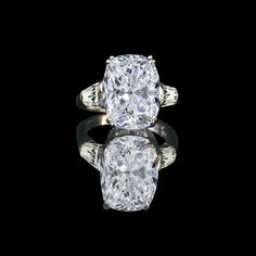 5 ct. Oval brilliant cushion center ring detailed with tapered baguette sides