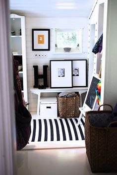 laundry/mud rooms - mud room white chalkboard easel woven baskets white bench black gallery frames black & white photography white black striped rug paneled walls white shelves