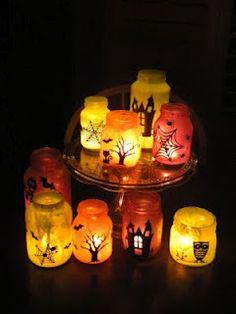 Today we got together and made Halloween luminaries - so fun!  First we mixed white glue and colored craft paint and painted the inside of glass jars.  Then we decorated the outside of the jars with black vinyl Halloween motifs cut on the Cricut....they are starting to look spooky!  Then we put candles in them and.......  ...turned out the lights! They are so cute and very spooky!!
