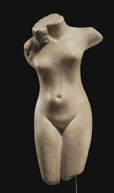 A ROMAN MARBLE TORSO OF VENUS   CIRCA 1ST-2ND CENTURY A.D.   The goddess depicted nude, originally standing with her weight on her left leg, her right slightly advanced, her torso with a fleshy paunch along her abdomen and a narrow waist, her left arm raised outward, her head turned sharply to her left, with long tresses of corkscrew curls framing her neck  8½ in. (21.6 cm.) high