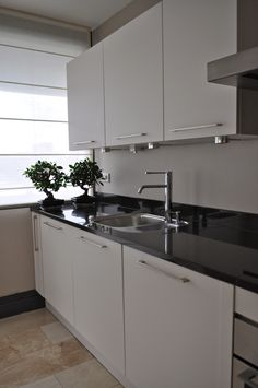 Witte hoogglans greeploze keuken met zwart gepolijst composieten werkblad in schiedam - Witte quartz werkblad ...