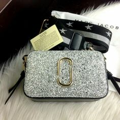 """Yang Di Tunggu~Tunggu..             ❤❤❤  NEW COLLECTION...    NEW SNAPSHOT... NEW MY JACOBS... Rp 300.000 Ready Stock New Arrival Marc By Marc Jacobs Snapshot Sequin Camera Bag SS17  #016 sz 18x10x7cm #M9614 WL #011 QUALITY SEMI PLATINUM 1:1 (Berdasarkan ORIGINAL) ONLY 2 COLOURS (RoseGold & Silver) MATERIAL: Calf Leather """"Gold Hardware"""" COMPLETED: 2 Strap (Stripe Strap & Classic), Certi,Dustbag Premium BERAT: 2 pcs (1 KG) BestSeller MJ in STORE!!! SUDAH TERJAMINNNN 👍🏻👍🏻👍🏻👍🏻👍🏻👍🏻"""