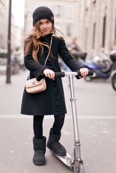 Chanel paired with a scooter. She looks perfectly put together in her Burberry peacoat and beanie.