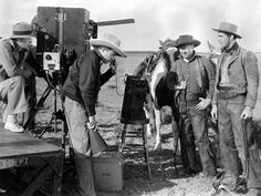 THE TEXAS RANGERS (1936) - Fred MacMurray & Jack Oakie await instructions from director King Vidor on location - Paramount - Production Still.